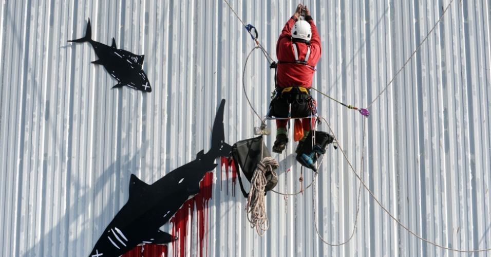 23.mai.2016 - Ativista da organização ambientalista não-governamental Greenpeace redesenha de vermelho o logotipo --que mostra um atum-- no prédio da fabrica de conservas da revendedora de frutos do mar Petit Navire, para protestar contra métodos de pesca em Douarnenez, oeste da França