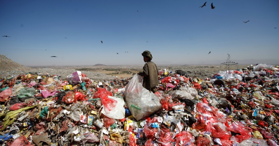 17.nov.2016 - Menino fica em pé sobre uma montanha de lixo em aterro sanitário nos arredores de Sanaa, no Iêmen
