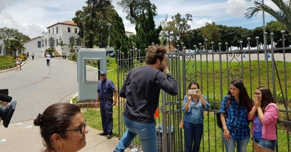 """3.dez.2016 - Candidatos correm para entrar antes do fechamento dos portões na PUC (Pontifícia Universidade Católica) de Minas Gerais. Um deles comemorou a entrada com uma pirueta e mandou beijos para os """"secadores"""" que esperavam os retardatários"""