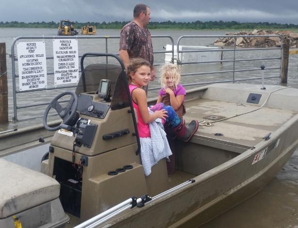 Mike Magee em seu barco com suas filhas antes de partir para missão de resgate de um amigo e quatro crianças, perto de Hamshire, Texas - Jennie Matthew/ AFP