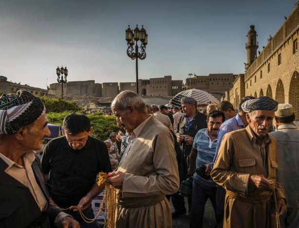Homens compram e vendem correntes de oração em frente à cidadela de Irbil, um local do Patrimônio Mundial da Unesco, na região do Curdistão iraquiano
