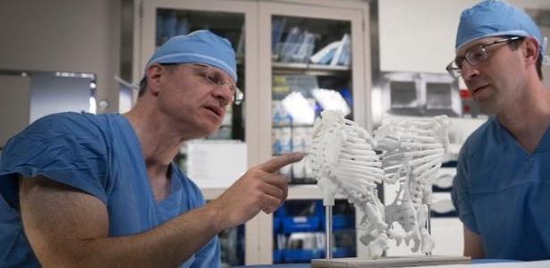 Allan Goldstein (esq.) e Brian Cummings discutem estratégia usando um modelo de gêmeos ligados pela estrutura óssea