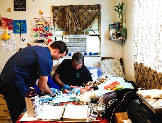 Beau Braden examina a pequena Juana Pascual durante uma visita domiciliar em Immokalee, Flórida