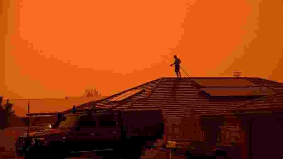 4.jan.2020 - Homem usa mangueira para molhar o telhado de casa em Nowra, em Nova Gales do Sul, na Austrália - Tracey Nearmy/Reuters