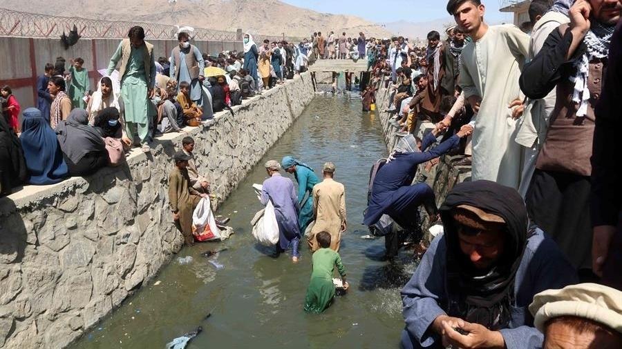 Afegãos caminham em vala com água suja para chegar ao aeroporto de Cabul - EFE/AKHTER GULFAM