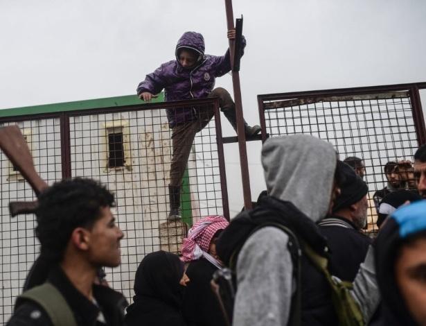 6.fev.2016 - Uma criança pula uma cerca perto da cidade de Azaz, na fronteira entre Síria e Turquia. Milhares de sírios enfrentaram o frio e a chuva para fugir de uma de uma ofensiva militar em Damasco, mas foram impedidos de atravessar a fronteira entre os países