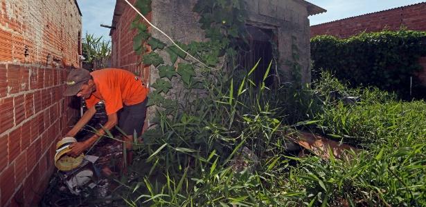 19.fev.2016 - Jorge Luiz Macedo, 56 anos, retira água parada na comunidade Zeppelin, em Santa Cruz, zona oeste do RJ, seis dias após visita de Dilma
