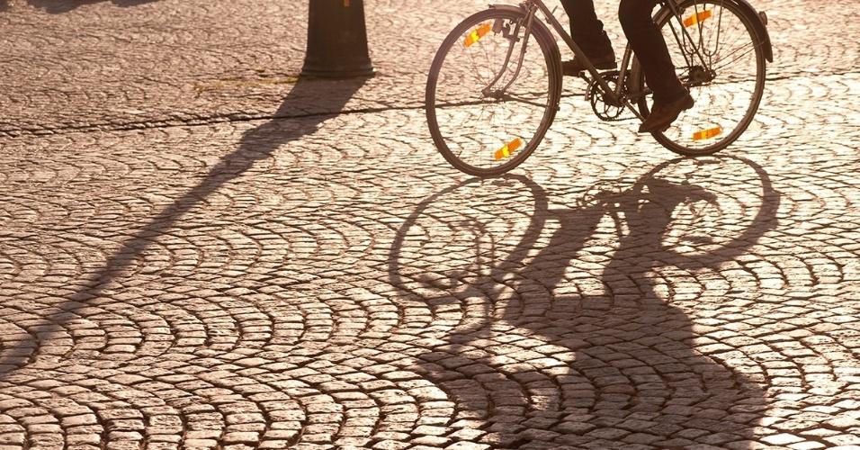 3.mai.2016 - Um ciclista passeia pelo calçamento da Praça do Mercado em Bruges, Bélgica. Na praça há um campanário do século 13, um dos primeiros exemplos da arquitetura neogótica, e muitos negócios locais