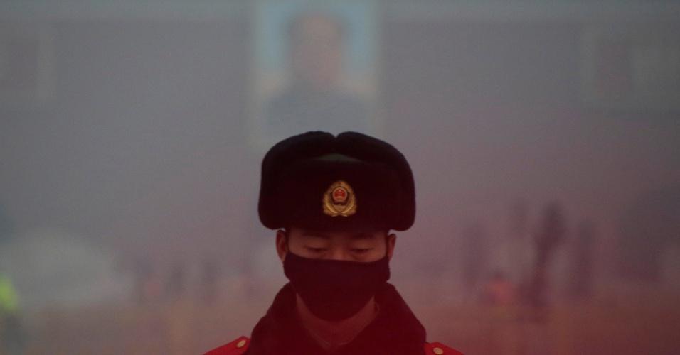 20.dez.2016 - Policial militar de guarda na Praça Tiananmen, usa máscara na frente de um retrato do falecido presidente Mao Zedong durante dia de alerta vermelho de poluição atmosférica em Pequim, na China