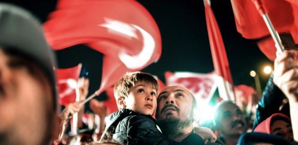 Homem segura criança enquanto acompanha discurso do presidente turco Recep Tayyip Erdogan