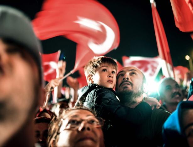 Homem segura criança enquanto acompanha discurso do presidente  Erdogan  - Bulent Kilic/ AFP