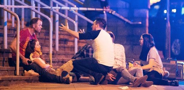 Jovens reagem após ataque em Manchester, no Reino Unido, na noite de segunda-feira (22)