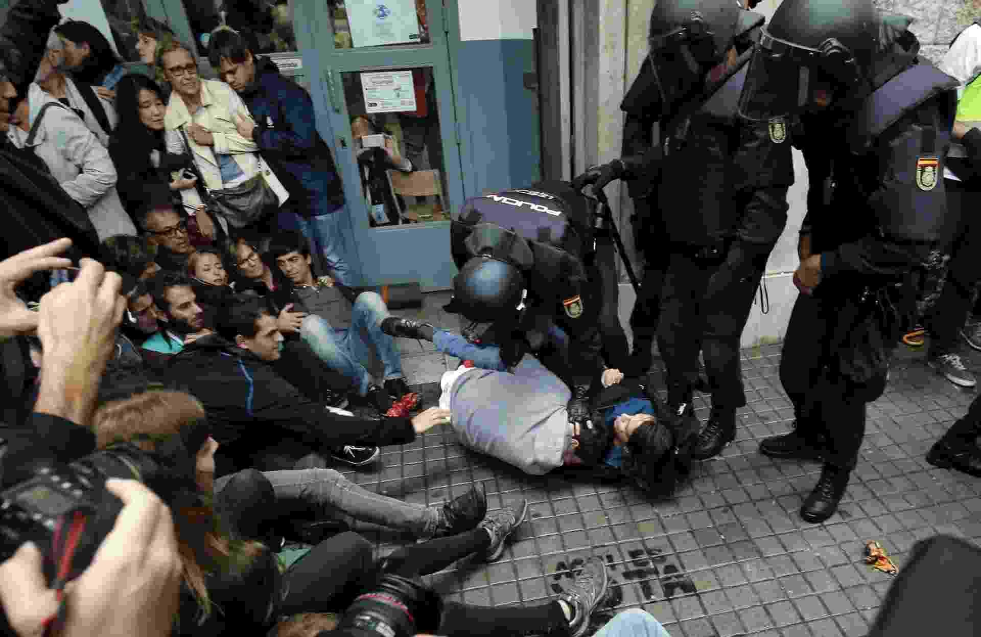 1º.out.2017 - Policiais espanhóis imobilizam duas pessoas do lado de fora de um local de votação em Barcelona, no dia de um referendo que vota a independência da Catalunha - Pau Barrena/AFP