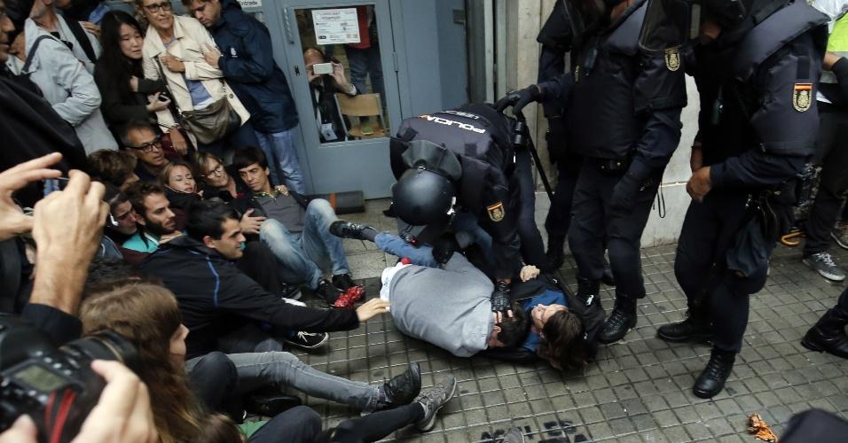 1º.out.2017 - Policiais espanhóis imobilizam duas pessoas do lado de fora de um local de votação em Barcelona, no dia de um referendo que vota a independência da Catalunha