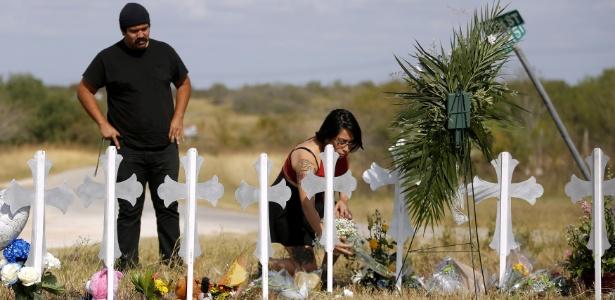 Mulher deposita flores em memorial para as vítimas do atirador que atacou uma igreja no Texas