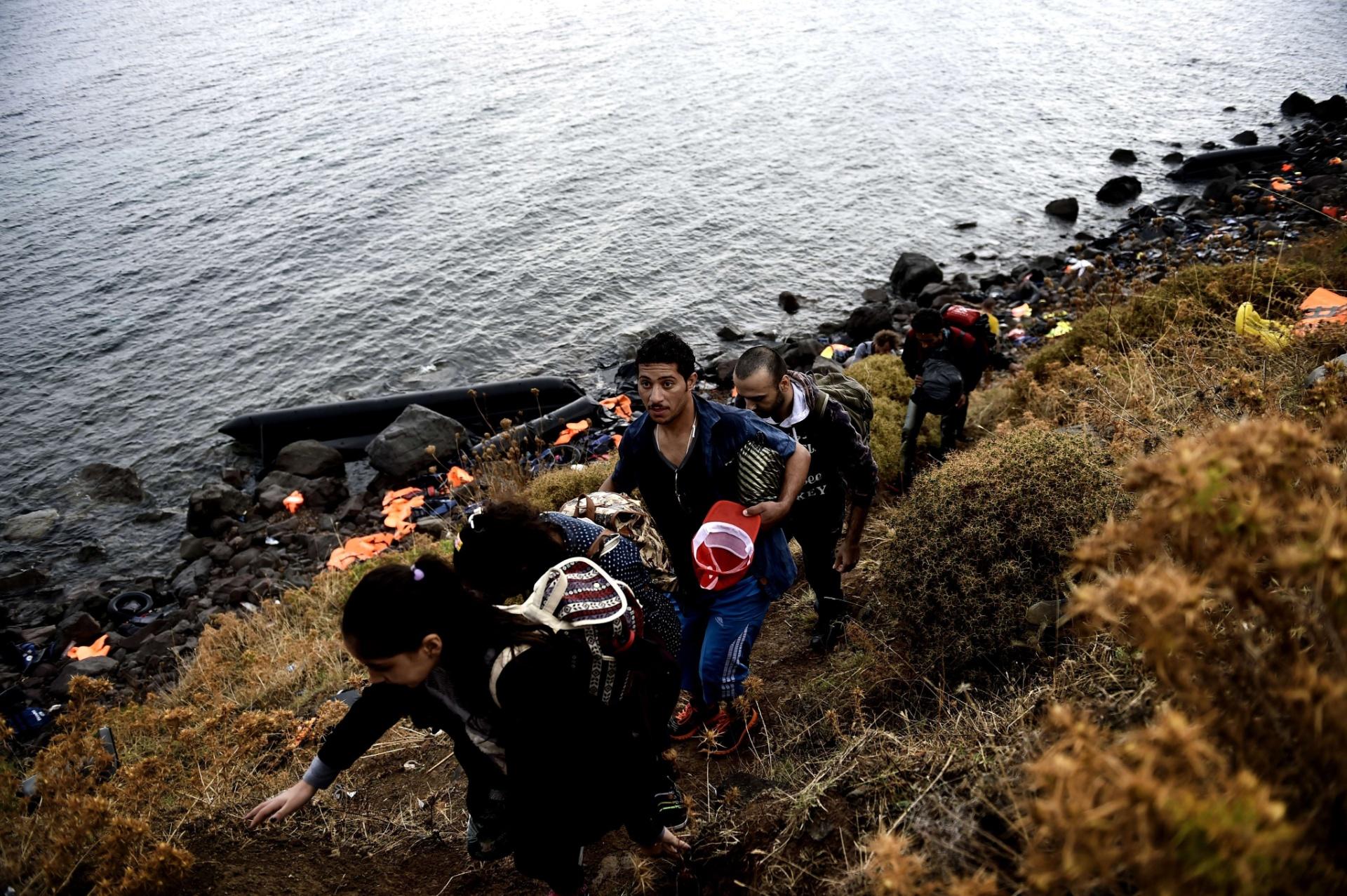 28.set.2015 - Refugiados sírios sobem colina na ilha de Lesbos, na Grécia, depois de atravessarem o mar Egeu, vindos da Turquia. Uma embarcação com imigrantes afundou e deixou dezenas de mortos