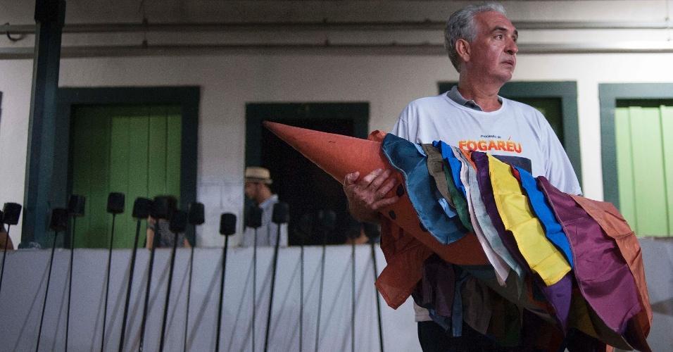 23.mar.2016 - Voluntário carrega vestimentas dos cerca de 40 farricocos que participam do tradicional Fogaréu de Goiás. Ao fundo, as tochas que também são símbolo da procissão