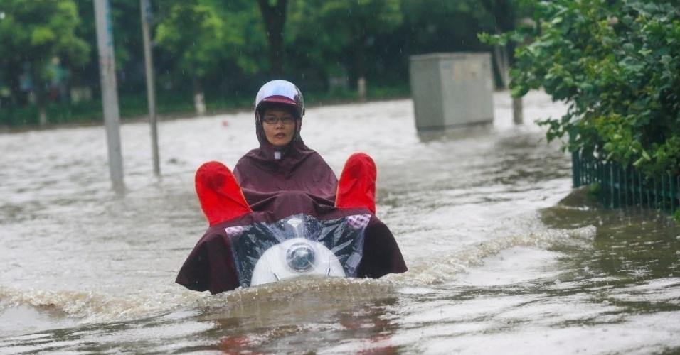 15.jun.2016 - Uma moradora de Liuzhou, na China, enfrenta a enchente após colocar uma capa como proteção para seu corpo e sua moto