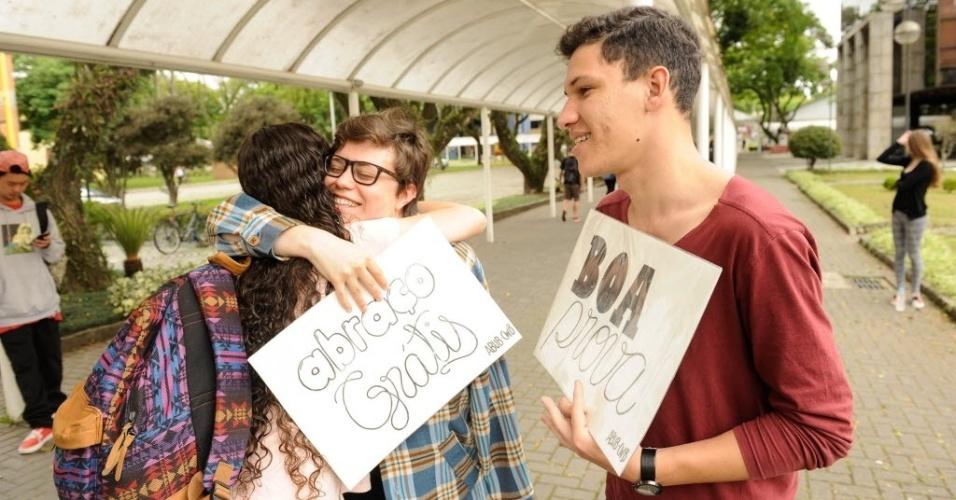 6.nov.2016 - Daniel Peticor e Elisama Koppe, ambos de 21 anos e estudantes da Aliança Biblica Universitária Brasileira pelo segundo ano distribuem abraços grátis aos candidatos do Enem que chegam para fazer a prova na PUC de Curitiba, neste domingo (6)