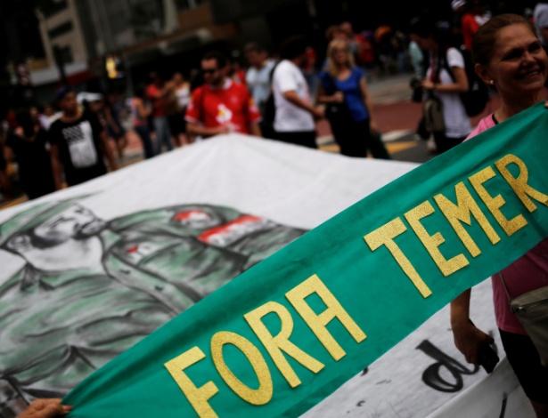 """Mulher segura faixa que diz """"Fora Temer"""" ao lado de homenagem a Fidel Castro durante protesto na avenida Paulista, em São Paulo  - Nacho Doce/Reuters"""