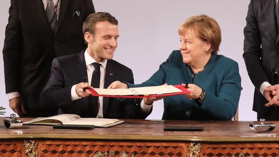 22.jan.2019 - O presidente da França, Emmanuel Macron, e a chanceler alemã, Angela Merkel, assinam o tratado franco-alemã na cidade de Aache, na Alemanha - AFP