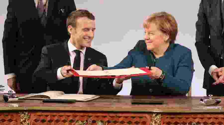 22.jan.2019 - O presidente da França, Emmanuel Macron, e a chanceler alemã, Angela Merkel, assinam o tratado franco-alemão na cidade de Aachen, na Alemanha - AFP