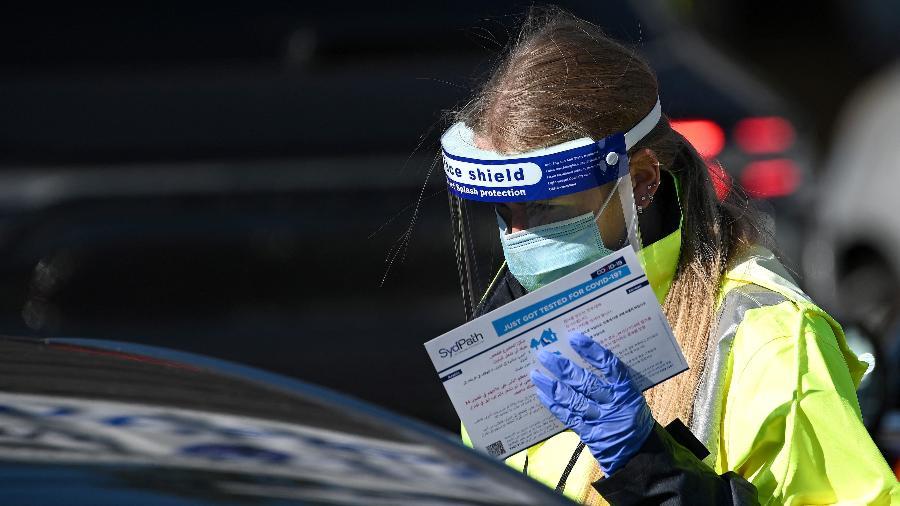 17.jun.2021 - Trabalhadora da saúde registra morador em unidade de teste de covid-19 em Bondi Beach, Sydney - Saeed Khan/AFP