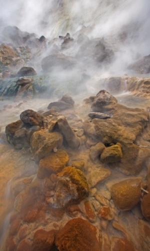 19.out.2015 - Após uma erupção no Vale dos Gêiseres, em Kamchatka, Rússia, o vapor da água flui sobre rochas manchadas de algas e bactérias. Argila vulcânica, minerais na água e microorganismos nas cachoeiras e nascentes contribuem para a paleta de cores