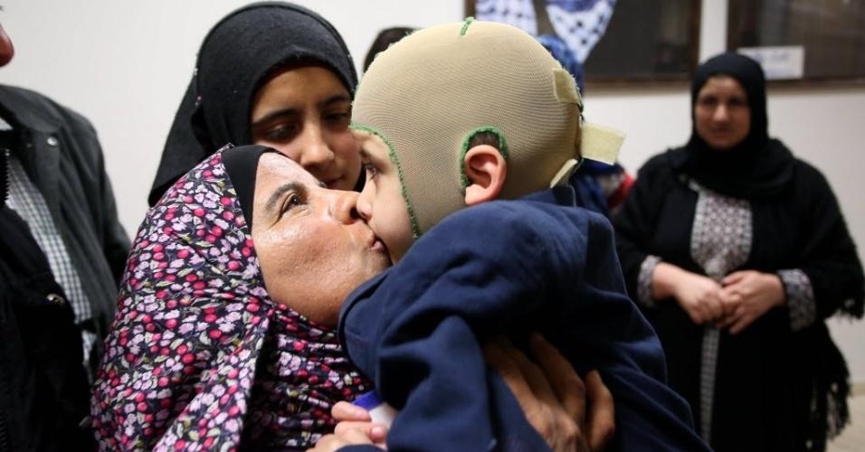 15.mar.2016 - Mulher beija menino palestino Ahmed Dawabsha, o único sobrevivente do incêndio criminoso na cidade de Nablus, Cisjordânia. A casa da família Dawabsha foi incendiada supostamente por colonos judeus em julho de 2015. Os pais e o irmão de um ano de Ahmed morreram queimados. Os responsáveis pelo ataque picharam a palavra