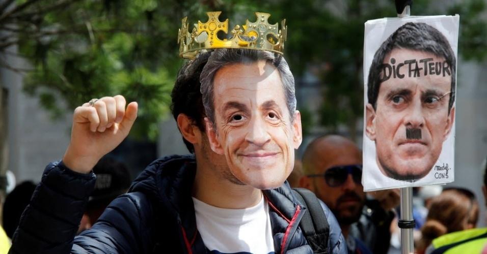 26.mai.2016 - Estudante francês usa máscara com o rosto do ex-presidente francês Nicolas Sarkozy e segura um cartaz com o rosto do primeiro-ministro francês Manuel Valls durante protesto contra a reforma da lei trabalhista, em Marselha, França