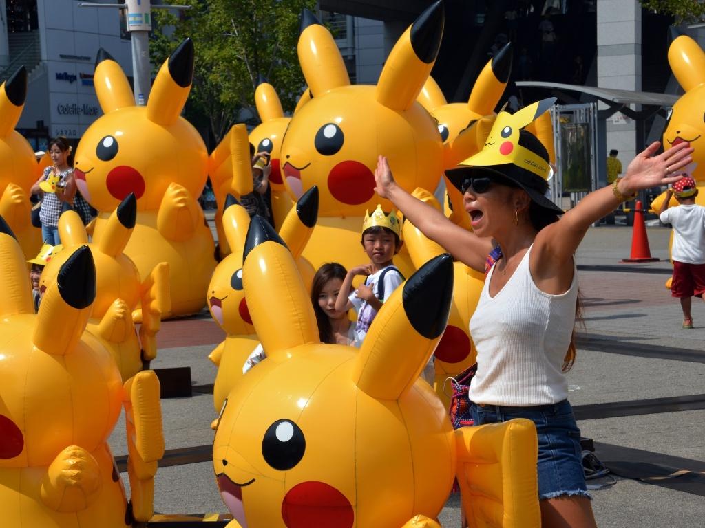 """10.ago.2016 - Mulher brinca entre balões do Pikachu instalados em Yokohama, no Japão. As esculturas do Pokémon são colocadas ao lado de um shopping todos os dias para atrair turistas durante um evento chamado de """"Grande Surto de Pikachus"""""""