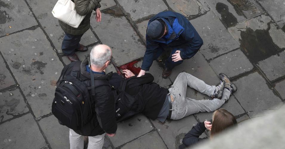 22.mar.2017 - Um homem ferido é assistido por transeuntes após um possível atentado terrorista na ponte Westminster, em Londres