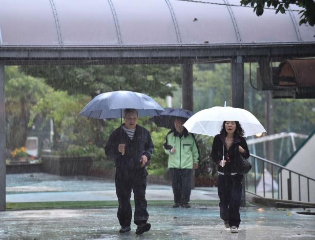 Japoneses enfrentam chuva a caminho de posto de votação em Tóquio, neste domingo