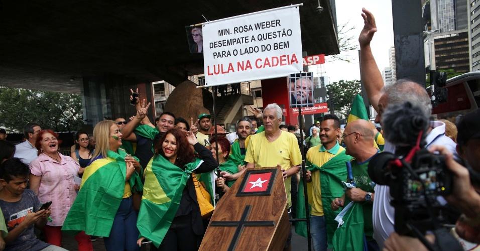 3.abr.2018 - Manifestantes carregam um caixão e uma placa onde se lê