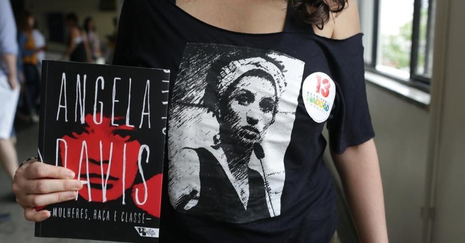 28.out.2018 - Eleitora de Fernando Haddad (PT) veste camiseta com o rosto da vereadora Marielle Franco e leva livro para a votação em São Paulo