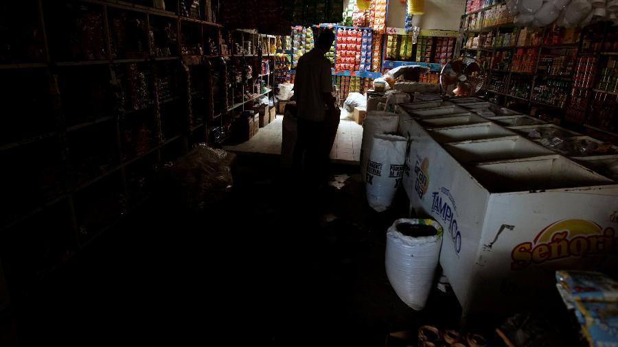 A silhueta de um homem em uma loja durante queda de energia em Tegucigalpa, Honduras - JORGE CABRERA/ REUTERS