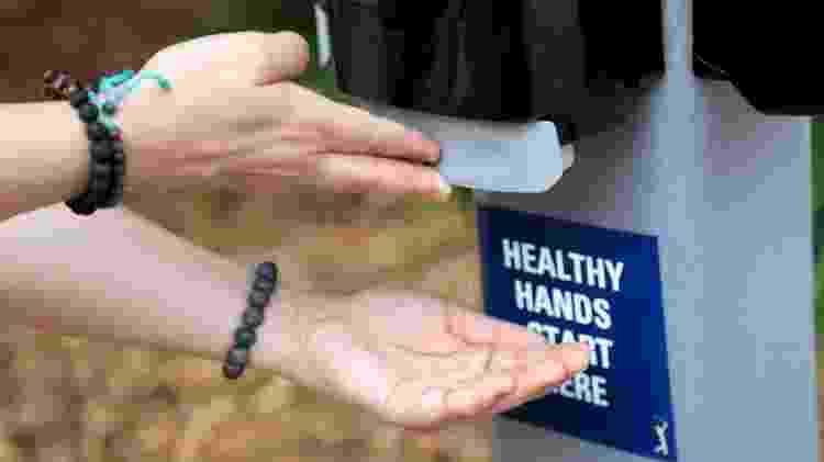 Pessoa aplica gel antibacteriano nas mãos - Getty Images - Getty Images