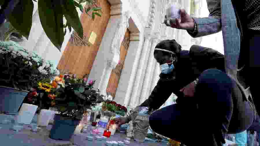 Várias pessoas colocaram flores e velas em frente à Basílica de Notre-Dame, em Nice, em homenagem às vítimas do atentado que deixou três mortos no local - Valery Hache/AFP