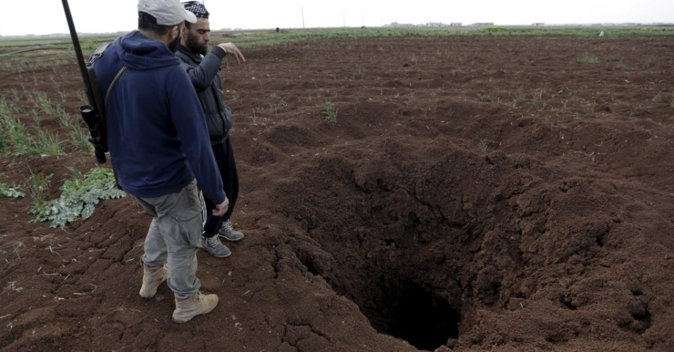 14.mar.2016 - Combatentes inspecionam buraco no chão após uma granada não detonar ao cair em uma fazenda na vila Mkahaleh, zona rural de Aleppo, na Síria