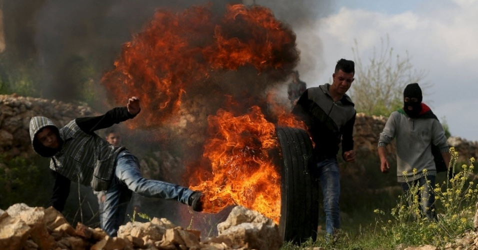 18.mar.2016 - Manifestantes palestinos empurram um pneu em chamas durante confrontos com tropas israelenses, na Cisjordânia