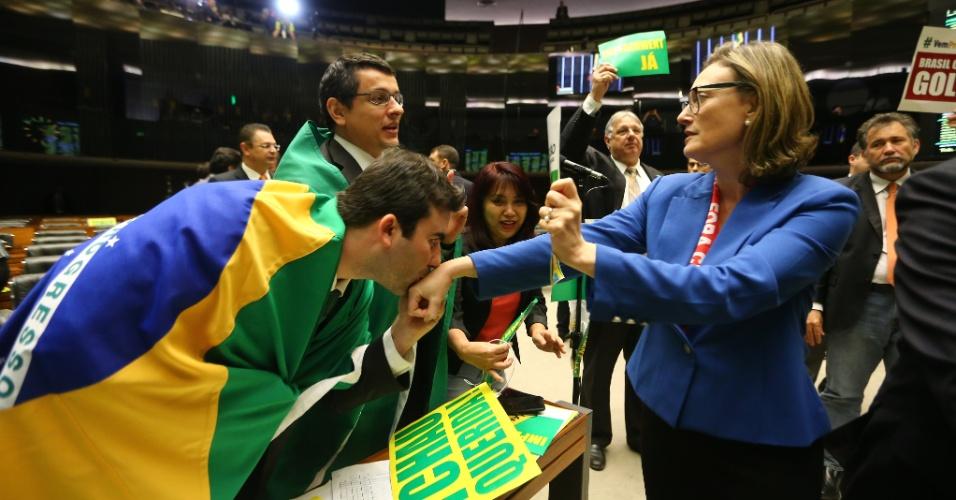 16.abr.2016 - O deputado Caio Nárcio (PSDB-MG), a favor do impeachment da presidente Dilma Rousseff, beija a mão da deputada Maria do Rosário (PT-RS), que é contrária ao processo, durante sessão que discute o afastamento a presidente do poder Executivo