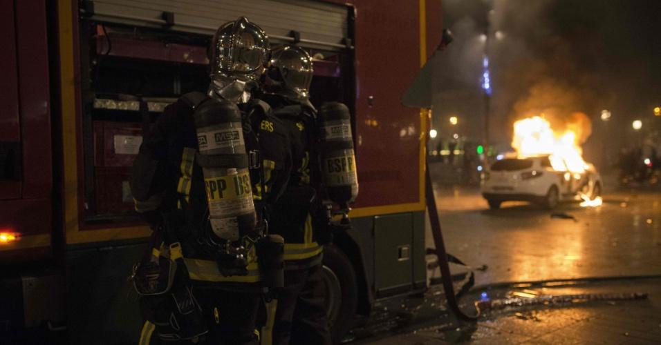 """23.abr.2016 - Bombeiros se preparam para combater fogo em carros incendiados na praça de la Republique, em Paris, em sequencia a um ato Nuit Debout (Noite Acordada). Os Nuit Debout, cada vez mais recorrentes na França, vêm sendo reprimidos pela polícia, que acusa a presença de """"desordeiros"""" entre os manifestantes. Os protestos começaram contra propostas do governo de reformas trabalhistas, porém as pautas se tornaram mais amplas e tidas como revolucionárias"""