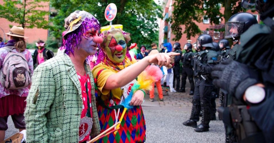 7.jul.2017 - Manifestantes vestidos de palhaço encaram policiais que delimitam área próxima ao local onde ocorre a reunião do G20