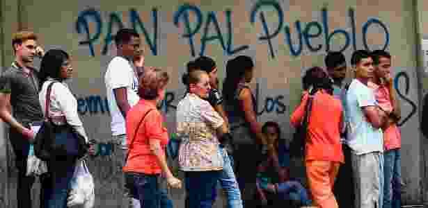 """Moradores de Caracas formam fila para comprar pão; atrás, é possível ler """"pão para o povo"""" pichado no muro - Juan Barreto/AFP - Juan Barreto/AFP"""