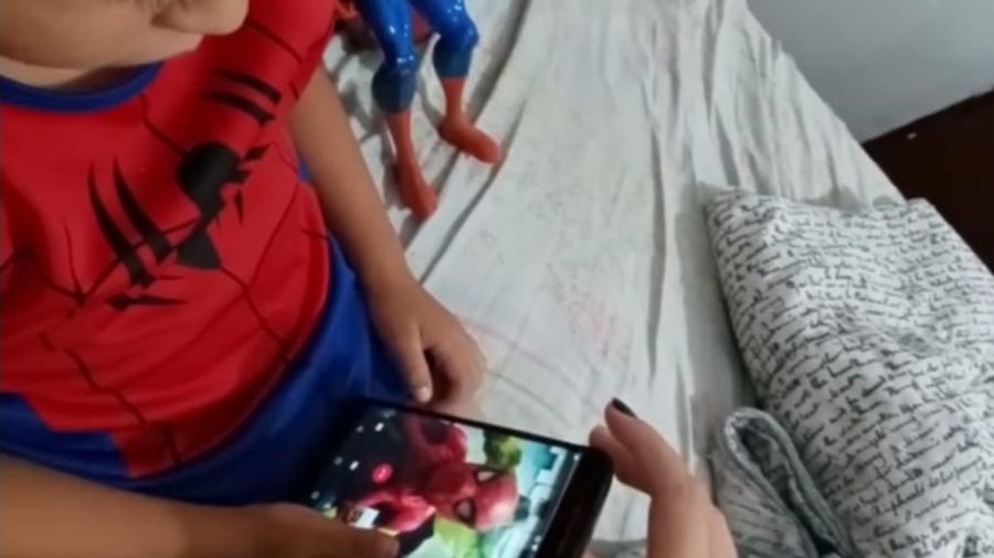 Criança olha o animador de festas infantis José Luís Fernandes caracterizado como Homem-Aranha pelo celular - Arquivo pessoal/ José Luís Fernandes