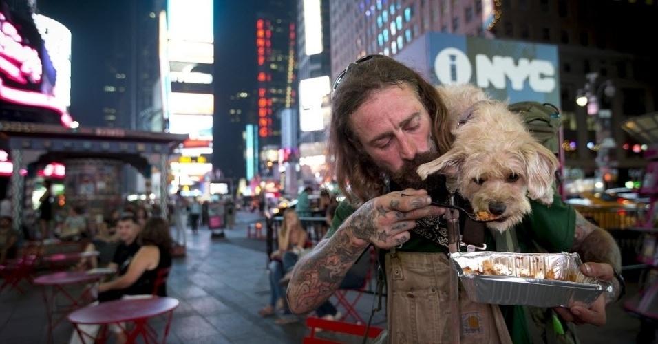 4.set.2015 - Deke Breuer alimenta seu cachorro Cahlupa com lasanha na Times Square, em Nova York. Breuer é de Detroit e dedicado sua vida a viajar nos últimos anos e ensinar alguns truques ao seu cão