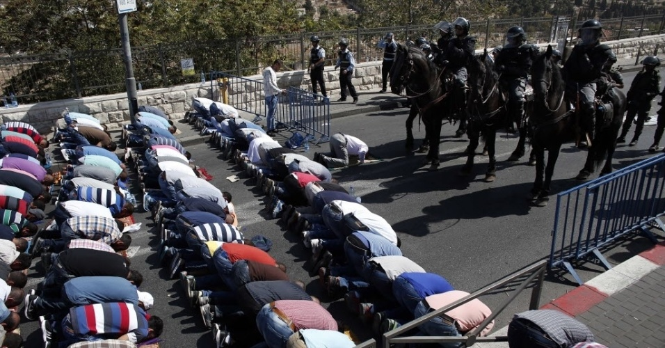 16.out.2015 - Palestinos fazem orações em frente a polícia israelense no bairro Wadi al-Joz, em Jerusalém. Uma restrição israelense proíbe que palestinos com menos de 40 anos de idade entrem na mesquita Al-Aqsa. O Conselho de Segurança da ONU vai realizar uma sessão especial para discutir a recente onda de violência entre israelenses e palestinos, que deixou 39 mortos ao longo das últimas duas semanas