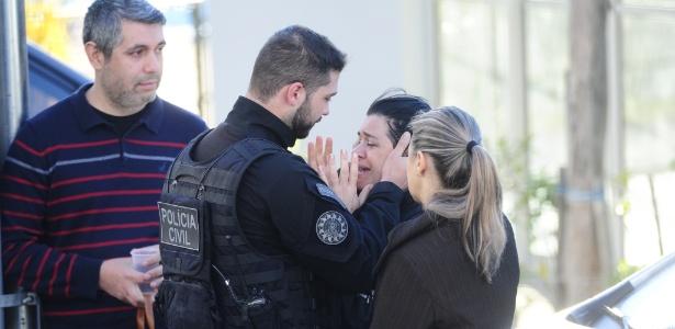 A mulher do policial civil Rodrigo Wilsen da Silveira, 39, a também policial Raquel Biscaglia é consolada após a morte do marido, em Gravataí, região metropolitana de Porto Alegre