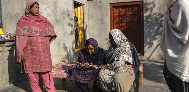 Mulheres paquistanesas consolam Nusrat Bibi que perdeu o filho Mazhar Hussain que morreu tentando migrar para a Itália