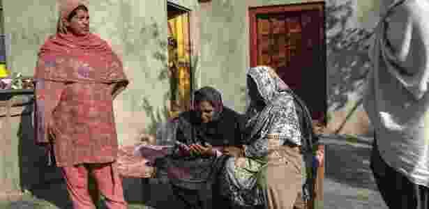 Mulheres paquistanesas consolam Nusrat Bibi que perdeu o filho Mazhar Hussain que morreu tentando migrar para a Itália - Sara Farid/The New York Times